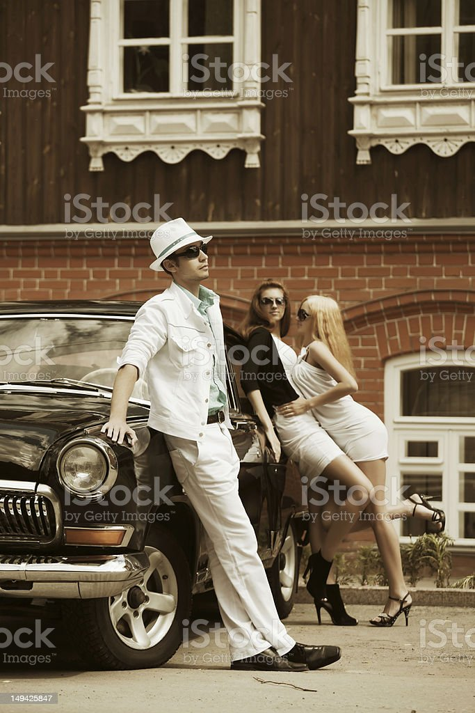 Young people with a retro car royalty-free stock photo