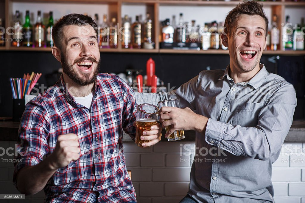 Young people with beer watching football in a bar stock photo