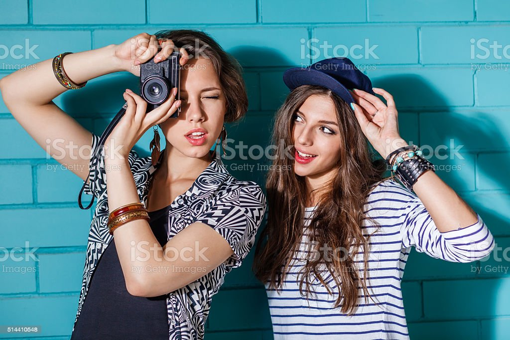 Young people with photo camera in front of blue wall stock photo