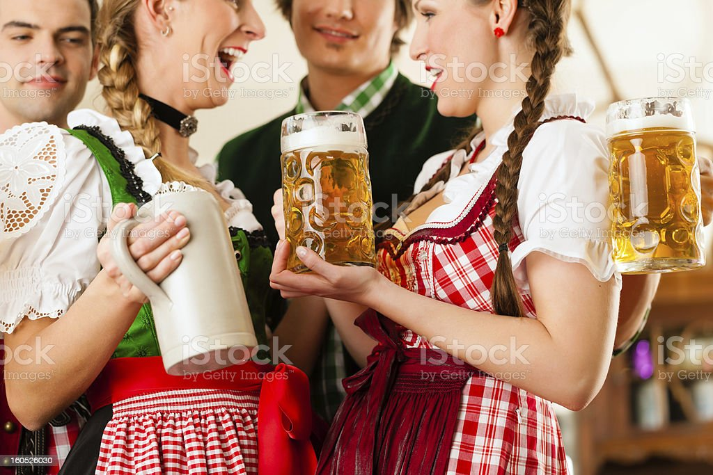 Young people with traditional Bavarian Tracht in restaurant or pub royalty-free stock photo