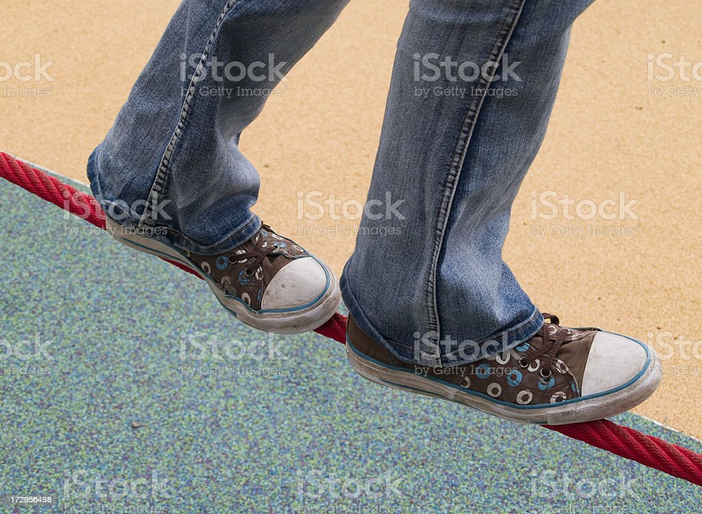 Young person balancing on low slung tightrope in playground. royalty-free stock photo