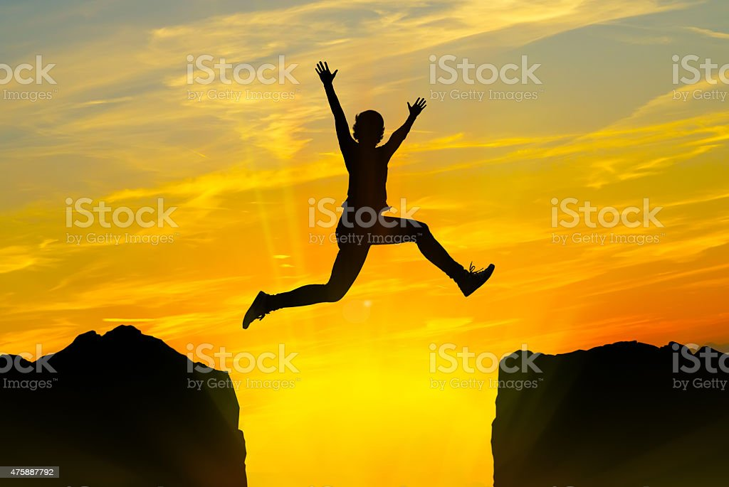 Young person jumping over the mountains stock photo