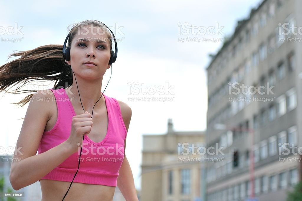 Young person listening music running in city street royalty-free stock photo