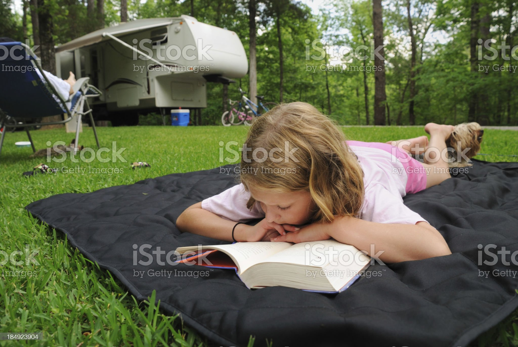 Young person reading on ground in campground royalty-free stock photo