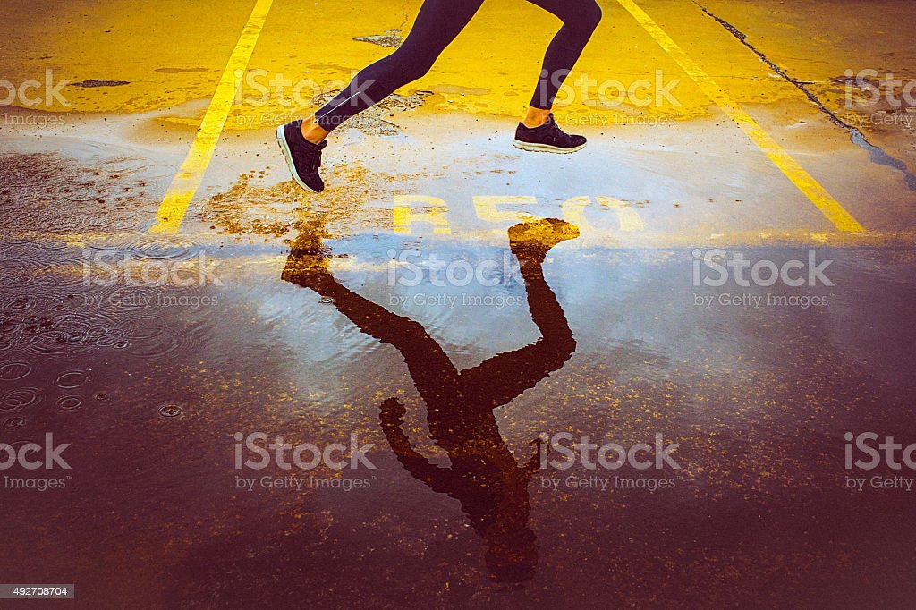 Young person running over the yellow parking lot. Black sport...