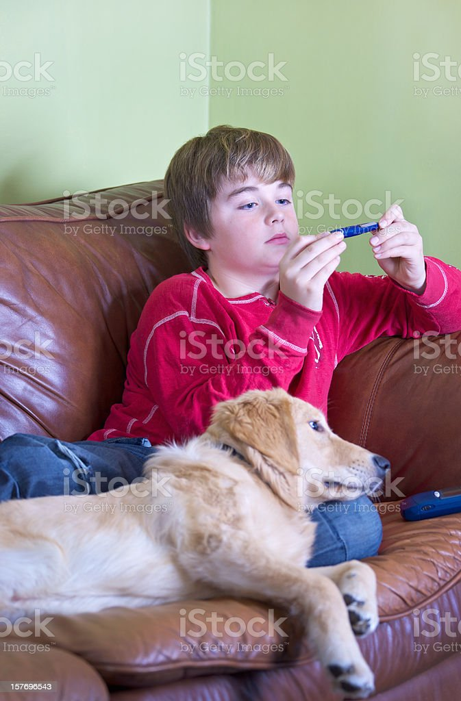 Young person with diabetes testing his blood sugar stock photo