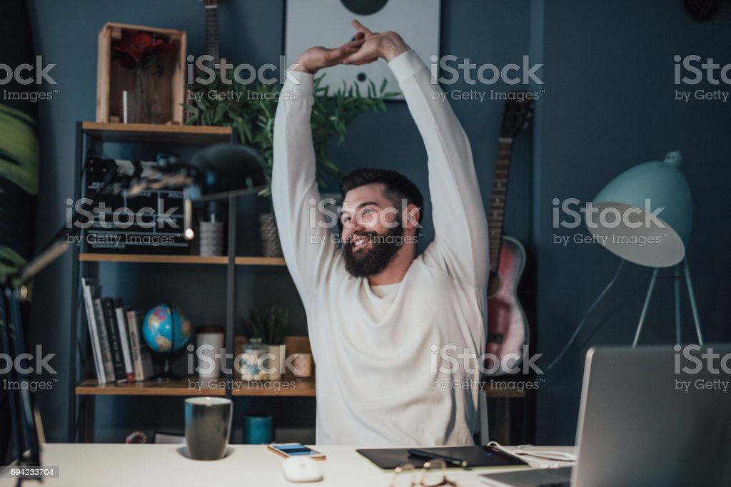 Young photo editor stretches his arms at the office after a long day of work stock photo
