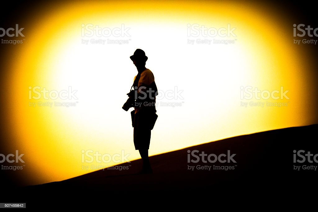 Young Photographer constantly on the move in the desert. stock photo