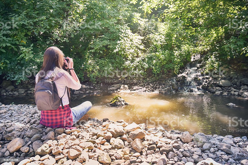 Young photographer in nature by the river stock photo