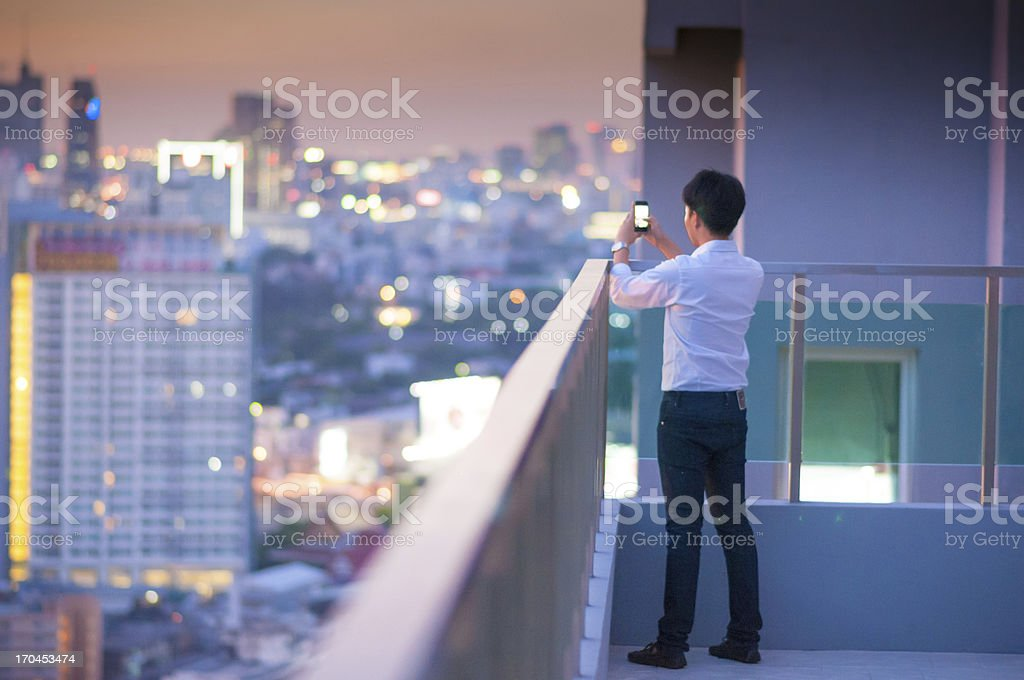 Young photographer with night light of big city stock photo