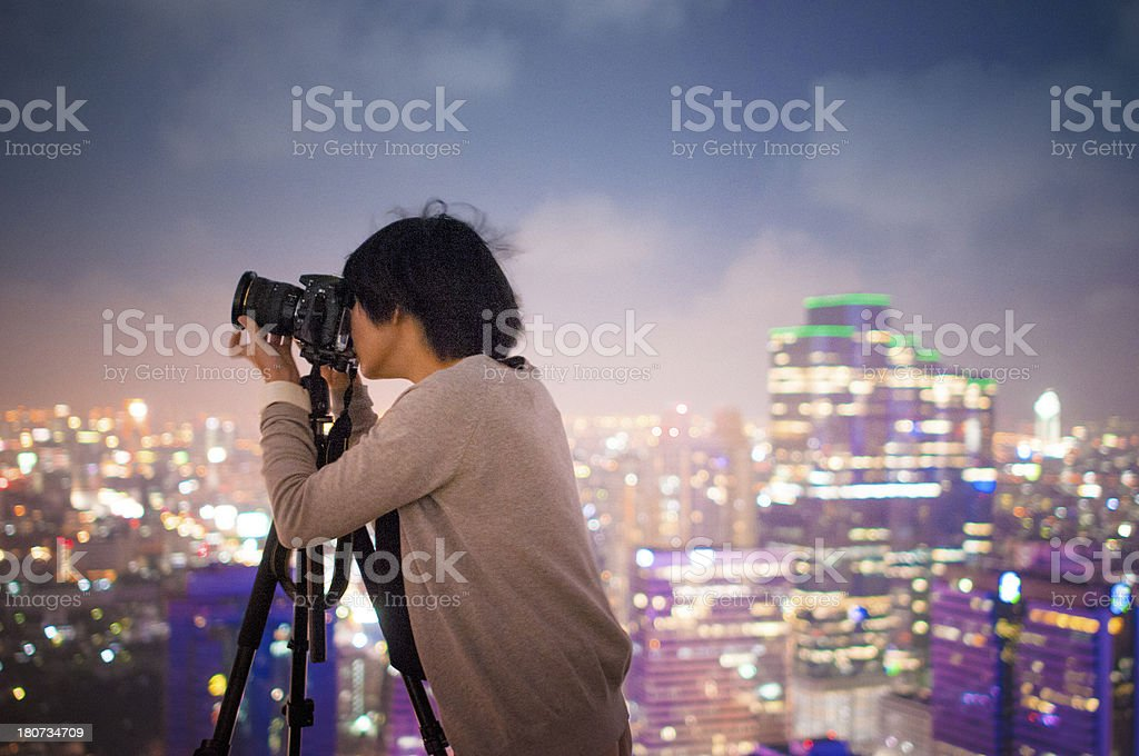Young photographer with night light of big city royalty-free stock photo