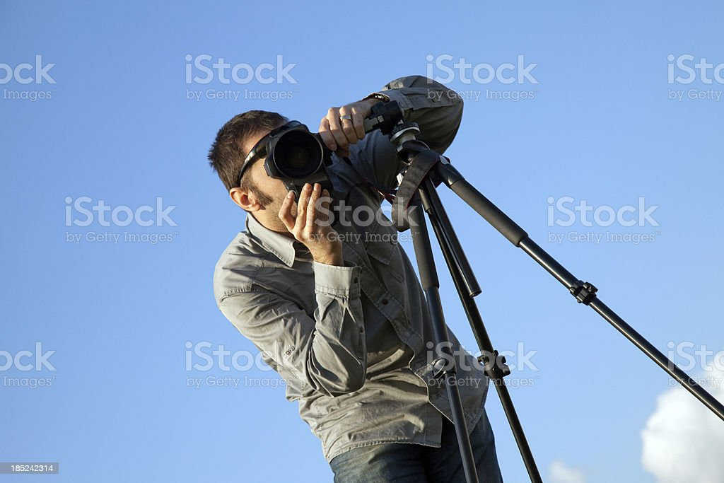 young photographer with the camera on a tripod. stock photo
