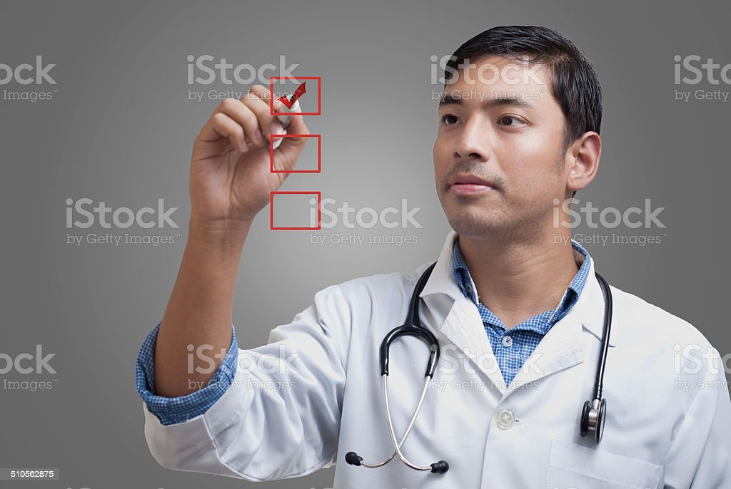 Young physician ticking the checklist boxes stock photo