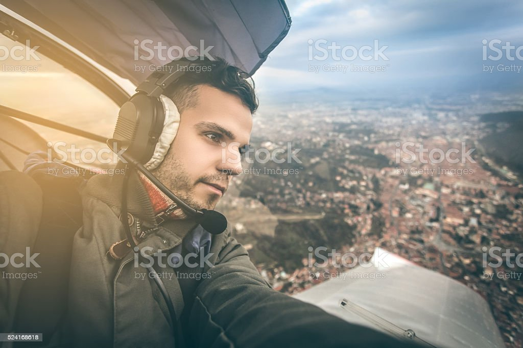 young pilot flying an ultra light model above the city, stock photo