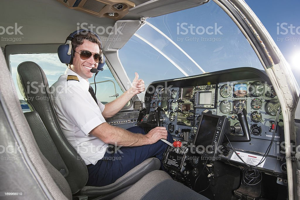 Young pilot in aircraft cockpit giving thumbs up stock photo