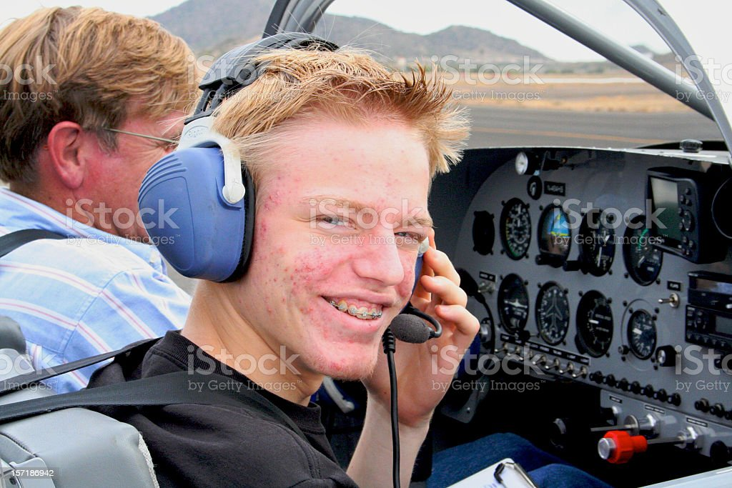 Young pilot in training sitting in a cockpit with instructor stock photo