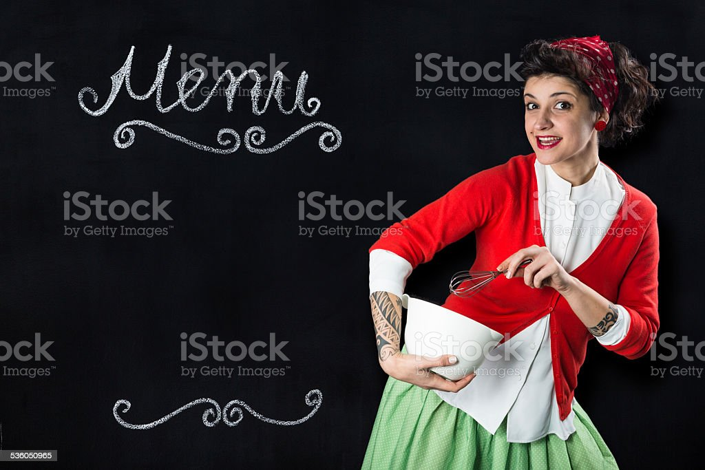 Young pin-up housewife in front of blackboard stock photo