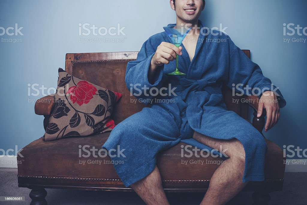 Young playboy in dressing gown toasting with cocktail royalty-free stock photo