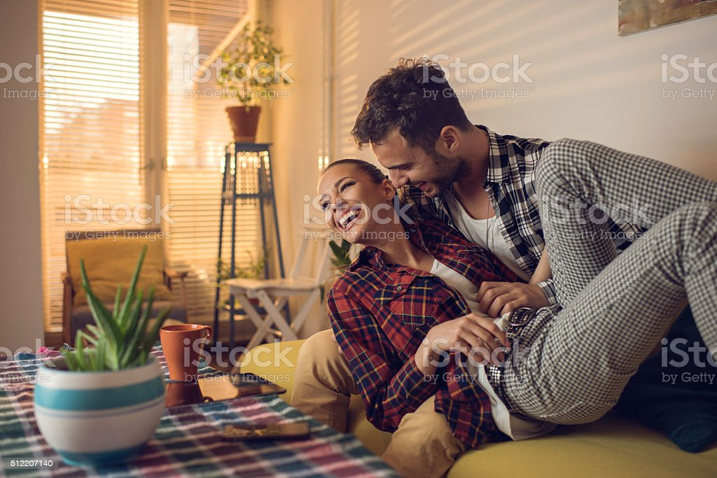 Young playful couple having fun together in the living room. stock photo