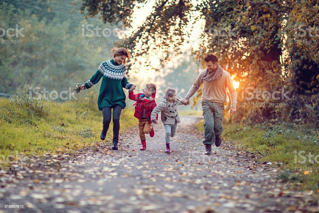 Young playful family having fun while running in the park. stock photo