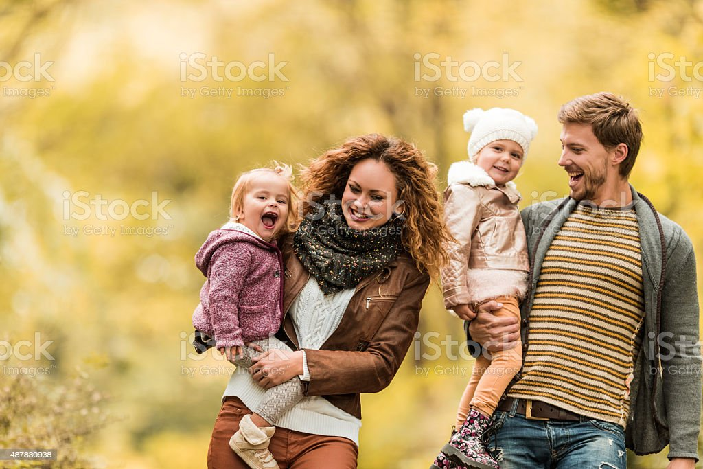 Young playful family taking a walk during autumn day. stock photo
