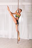 Young pole dancer in the studio