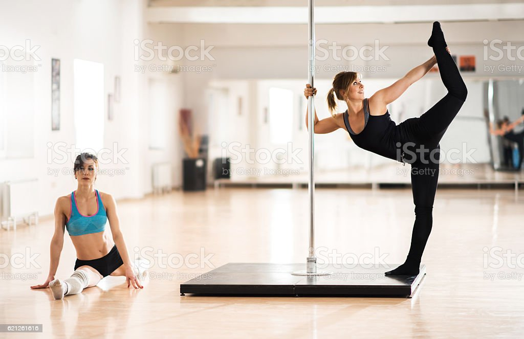 Young pole dancers warming up in a dance studio. stock photo