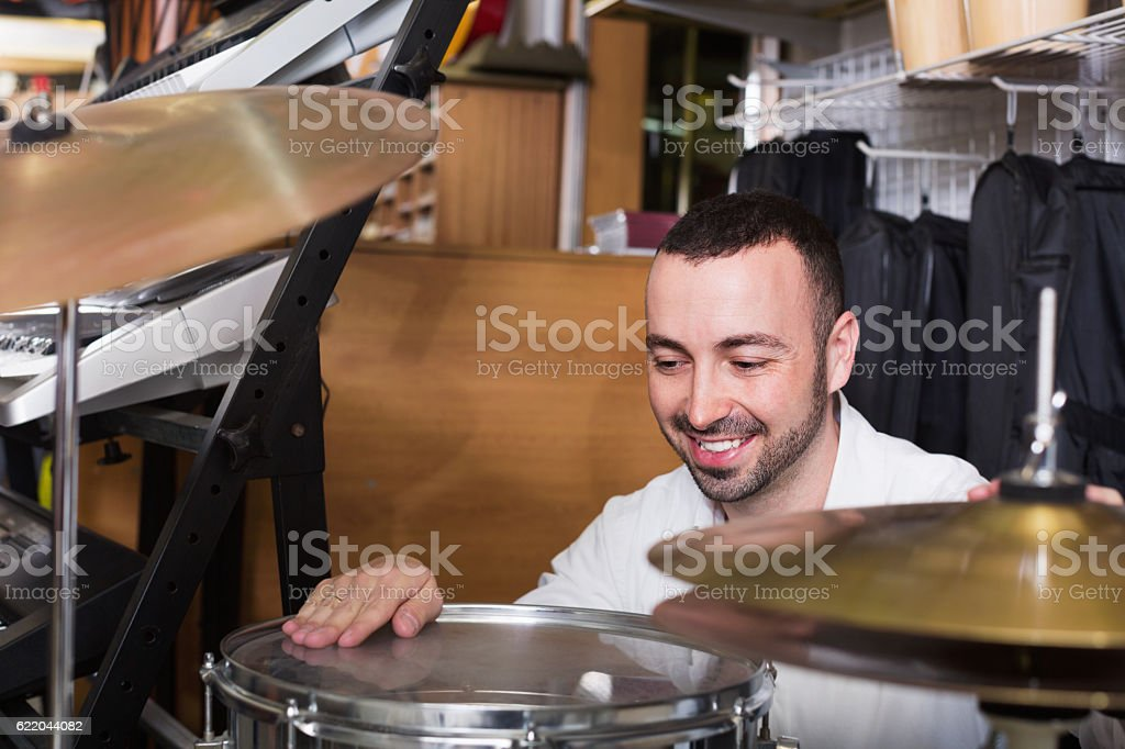 Young positive man  purchasing professional drum set stock photo