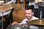 Young positive man  purchasing professional drum set