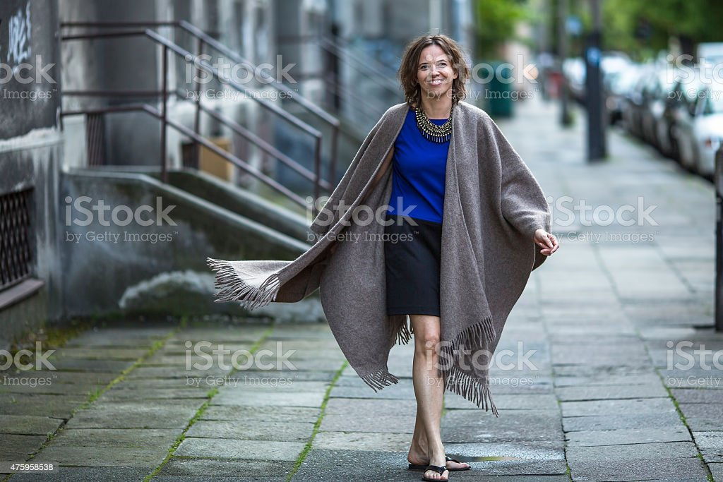Young positive woman in a poncho walking in the street. stock photo