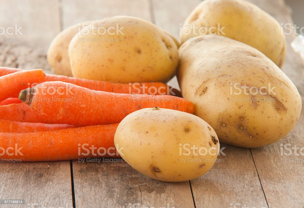 young potatoes and carrots on wooden background stock photo