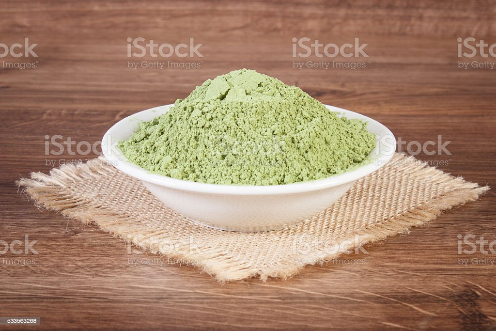 Young powder barley in glass bowl on jute canvas stock photo
