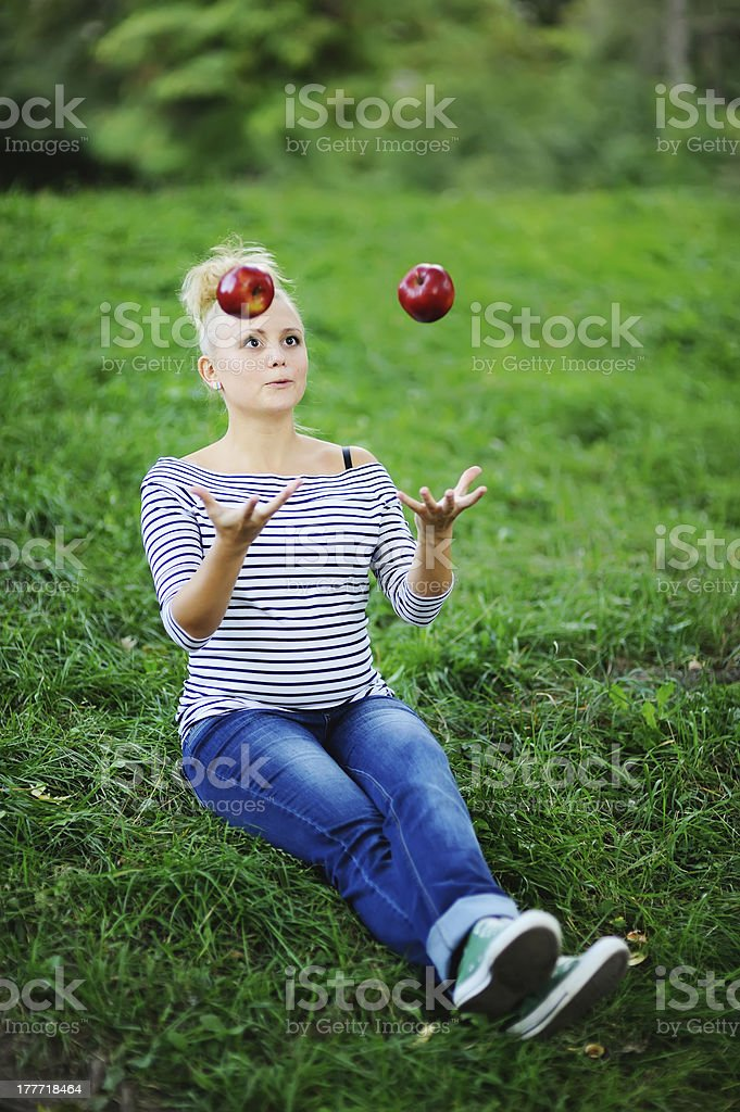 young pregnant juggles with apples royalty-free stock photo