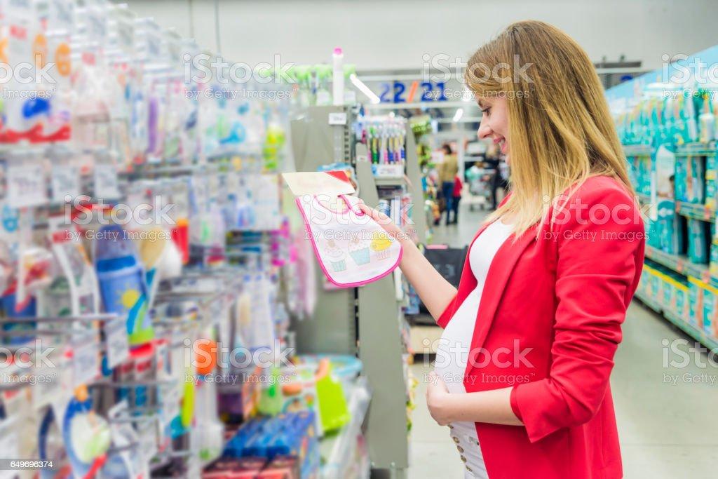 Young pregnant woman choosing baby bib at baby shop store stock photo