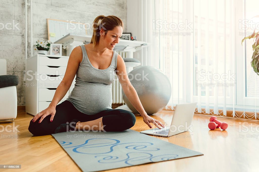 Young Pregnant Woman Exercises At Home. stock photo