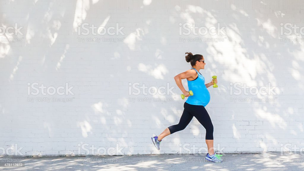 Young pregnant woman jogging down sidewalk in city. stock photo