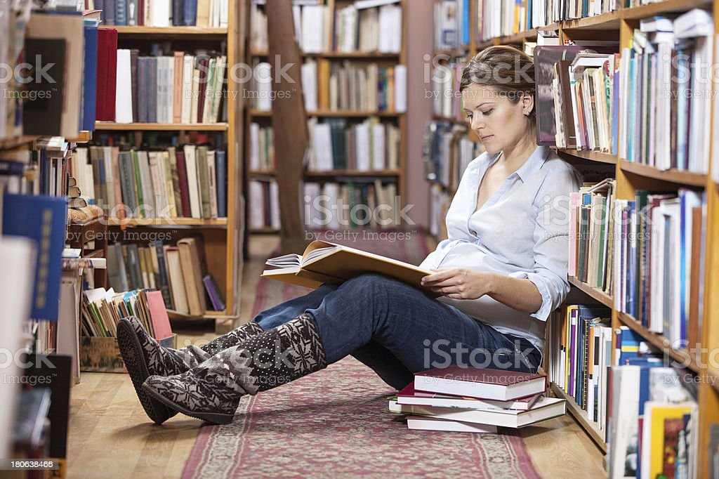 Young pregnant woman reading book in library royalty-free stock photo