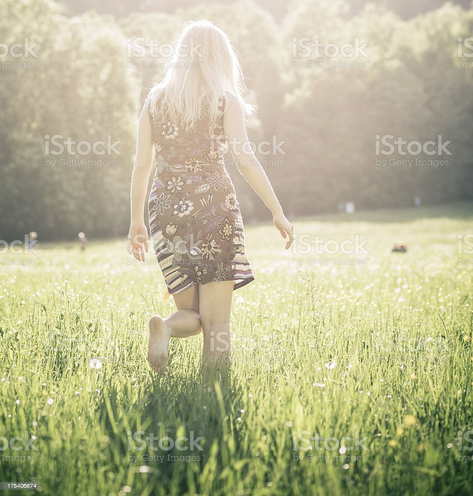 Young pregnant woman walking in the meadow stock photo