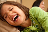 Young Preschool Girl Laughing Hysterically at Home