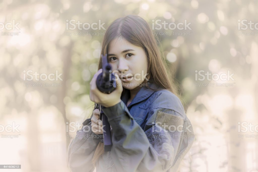 Young pretty Asian woman, in military pilot outfit, holding a rifle_Corrected stock photo
