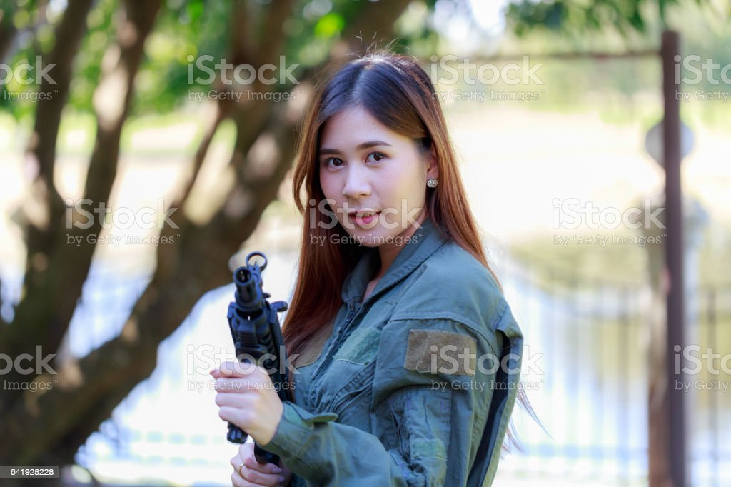 Young pretty Asian woman, in military pilot outfit, holding a rifle_Corrected. stock photo