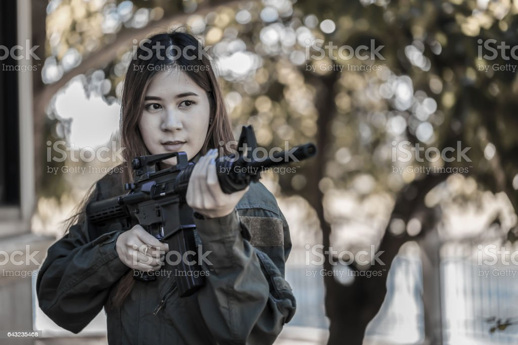 Young pretty Asian woman, in military pilot outfit, holding a rifle stock photo