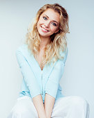 young pretty blond woman smiling on white background close up