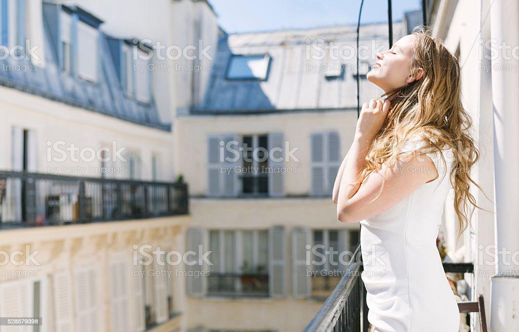 Young Pretty Blonde Girl in a Balcony Enjoying the Sun stock photo