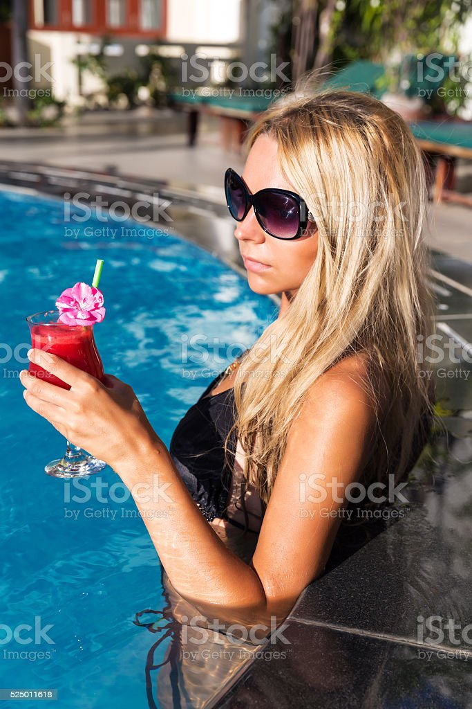 Young pretty blonde woman in swimming pool with coconut coctail stock photo