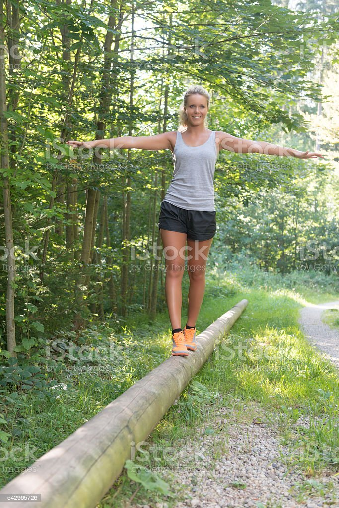 Young pretty blonde woman is exercising her balance in nature stock photo