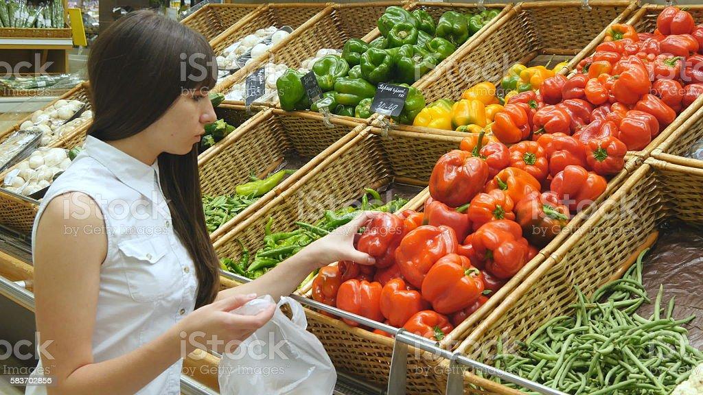 Young pretty girl is choosing peppers in a grocery supermarket foto de stock libre de derechos