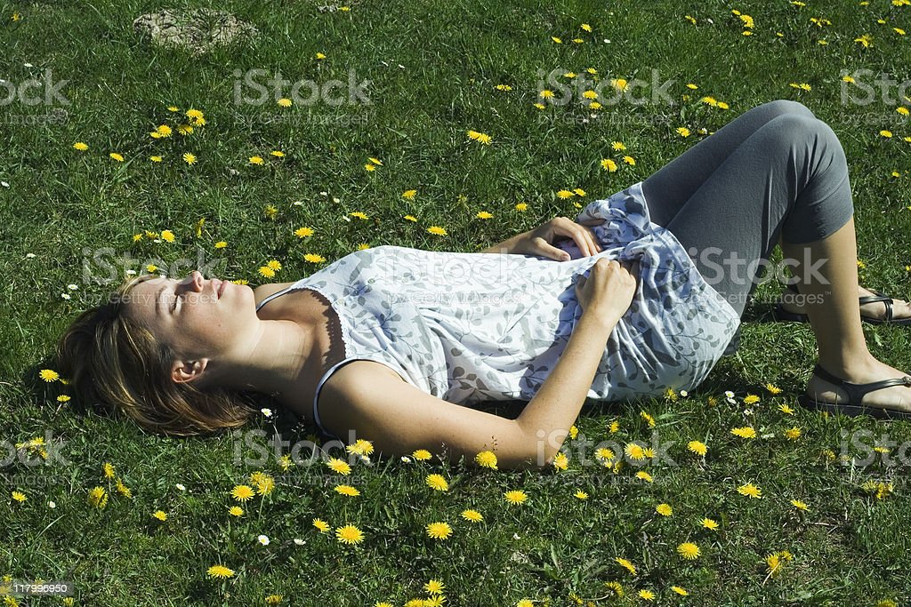 Young pretty girl lying in meadow with yellow flowers royalty-free stock photo