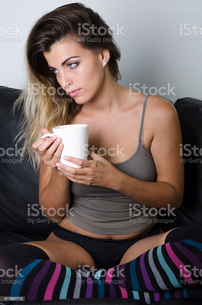 Young pretty girl with cup of coffee sitting in armchair stock photo