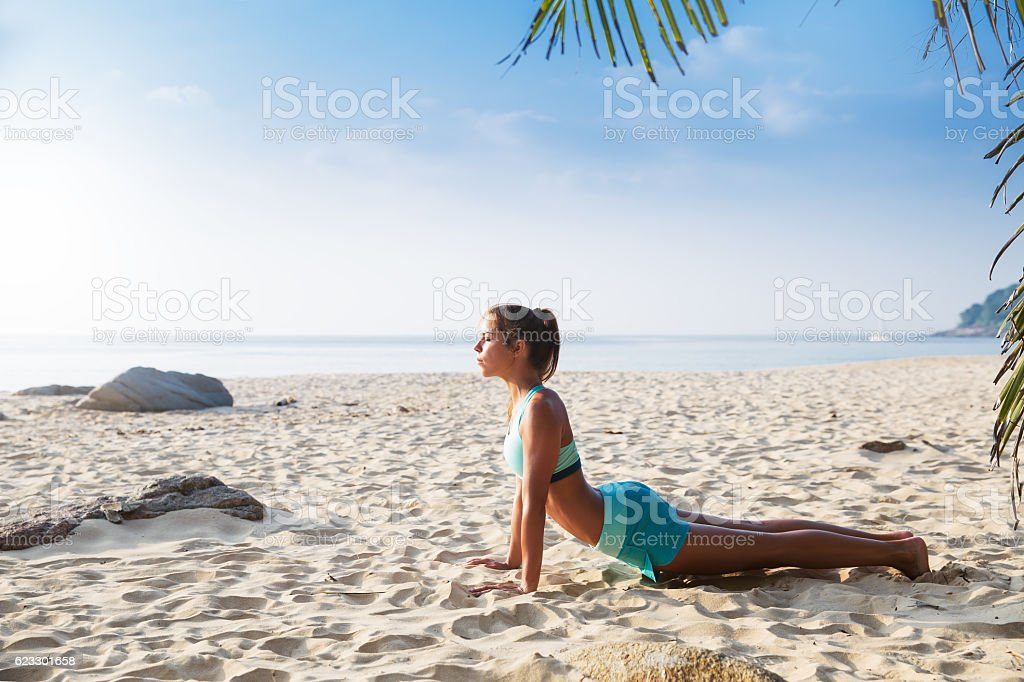 Young pretty slim brunette woman practise yoga pose tropical bea stock photo